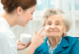 caregiver applying cream on patient's face
