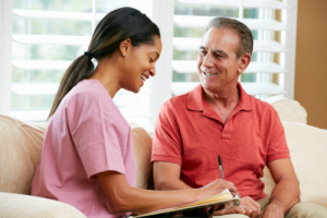 elderly man happily talking to a caregiver