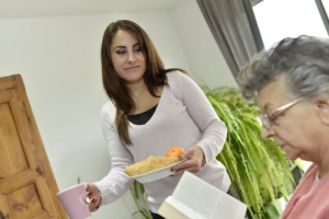 caregiver serving breakfast to elderly woman