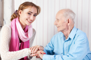 elderly man holding his caregiver's hands
